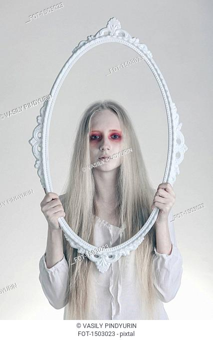 Portrait of woman with spooky red eyes holding picture frame against white background
