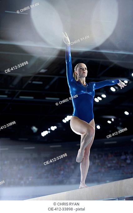 Female gymnast performing on balance beam in arena