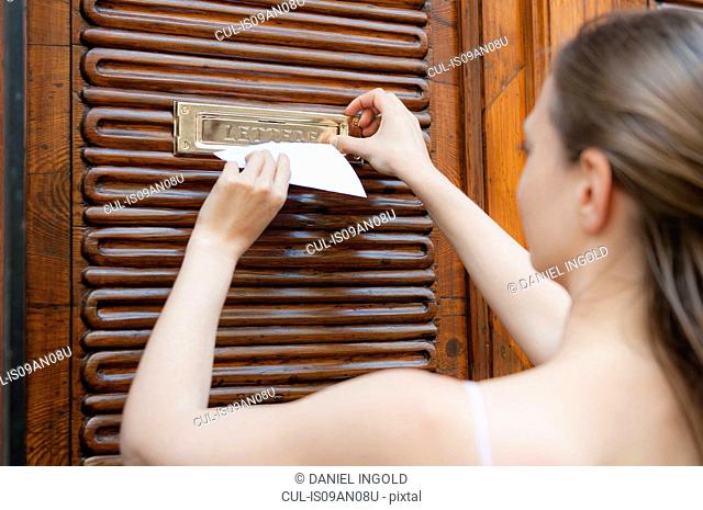 Over shoulder view of mid adult woman posting note through apartment mailbox, Sardinia, Italy