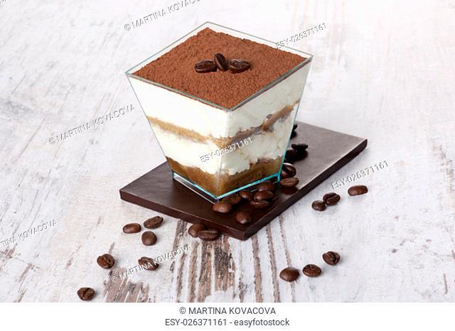 Tiramisu dessert with chocolate and coffee beans on white wooden textured table. Traditional tiramisu dessert, rustic, country style