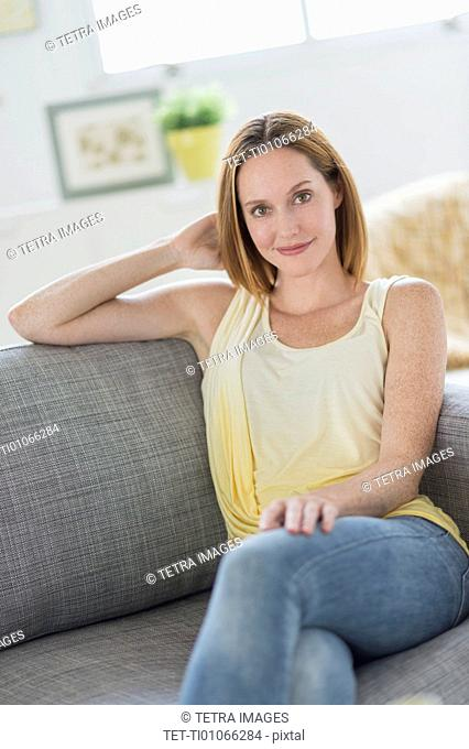 Portrait of young woman relaxing on sofa