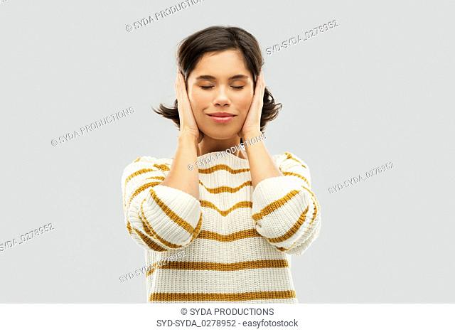 happy woman in pullover closing ears by hands