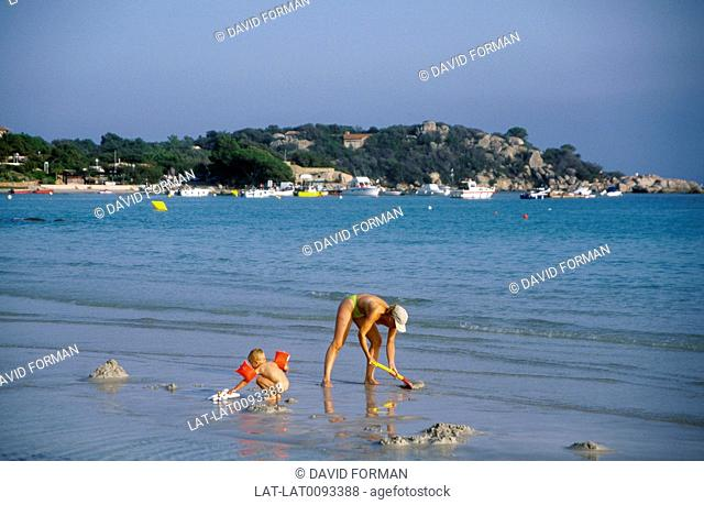 Beach. Woman and child on sand. Digging,buckets,spades