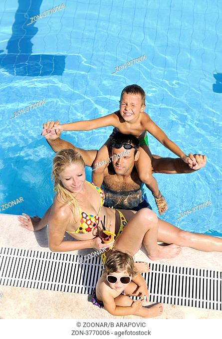 happy young family have fun on swimming pool at summer vacation