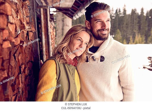 Couple standing outside log cabin in winter, Elmau, Bavaria, Germany