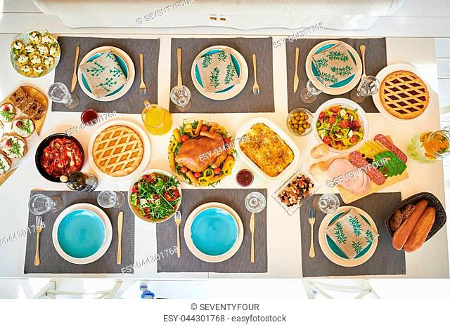 Top view of festive dinner table set for whole family with delicious homemade dishes, turkey and pies on it, served with robin blue plates and napkins