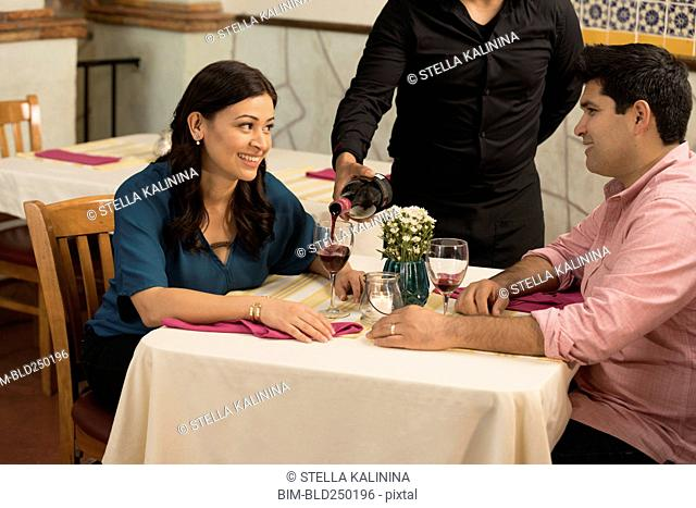 Waiter pouring wine for Hispanic couple in restaurant