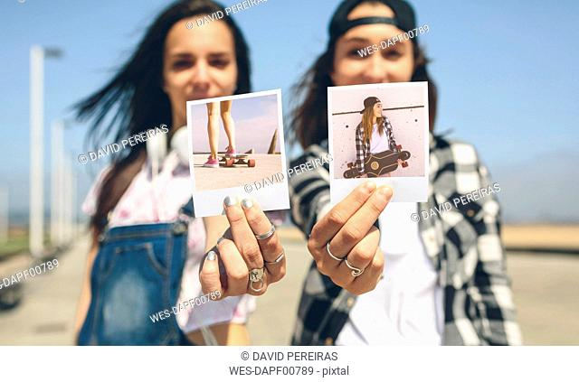 Two young women showing instant photos with their longboards