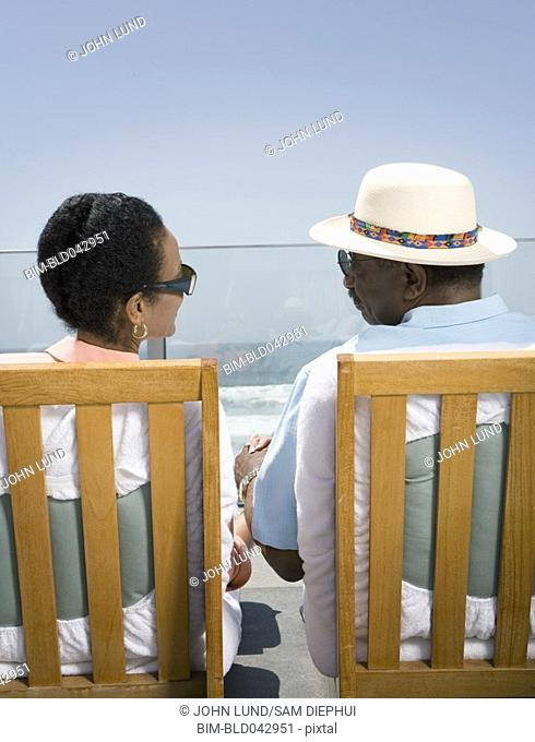 Senior African couple sitting in deck chairs