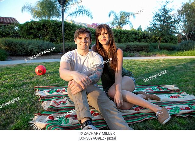 Portrait of young couple on picnic blanket in park