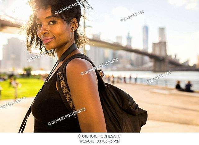 USA, New York City, Brooklyn, portrait of smiling woman at the waterfront