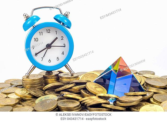 The glass pyramid and the table clock lie on a pile of ten-ruble Russian coins