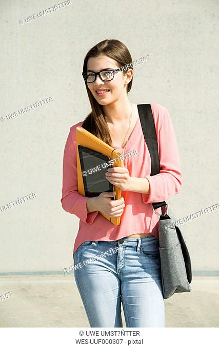 Brunette young woman with bag, folder and digital tablet outdoors