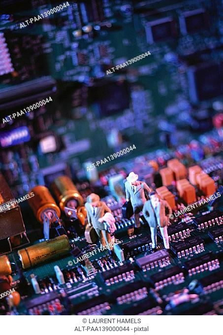 Toy figures on computer circuit board, close-up