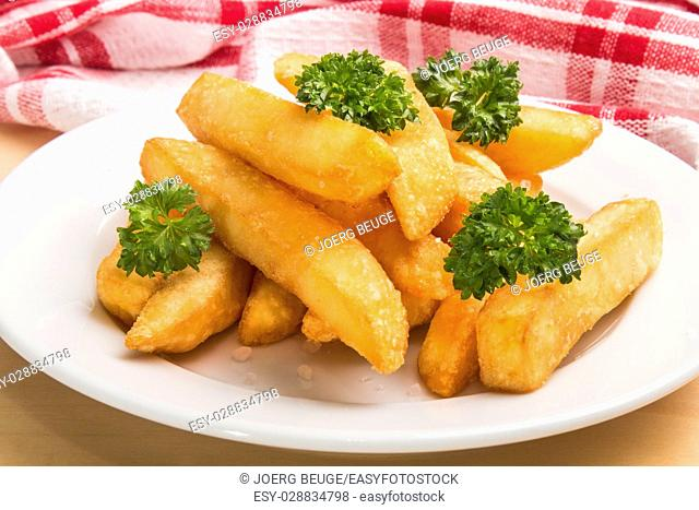 french fries with parsley on a white plate