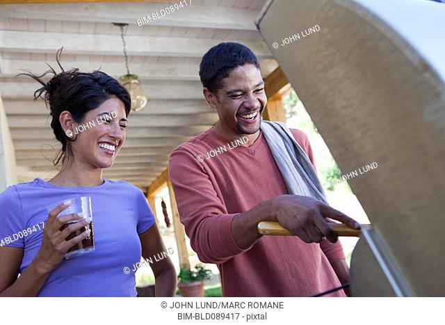 Smiling couple barbecuing together
