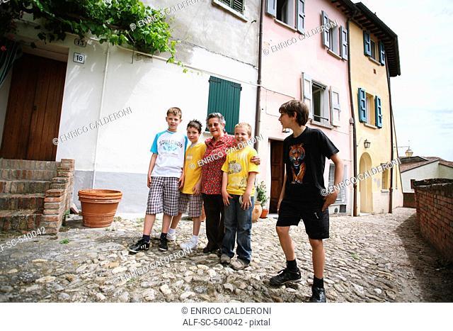 Senior Woman And Four Boys Posing In Street