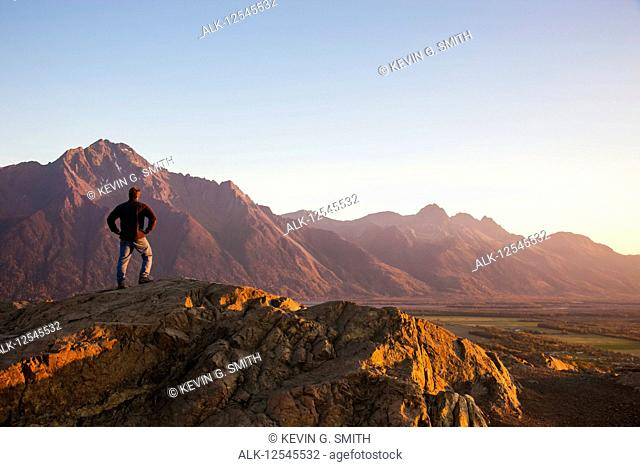 Man viewing scenery from the top of the Butte, Lazy Mountain in the background on a clear, sunny evening in autumn, South-central Alaska; Palmer, Alaska