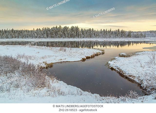 Forest reflecting in lake in winter, snow on the ground and on the trees, sky is very colorfull with red and orange, Gällivare, Swedish Lapland, Sweden