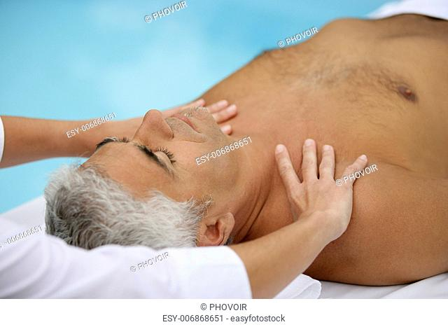 Mature man being massaged next to a swimming pool