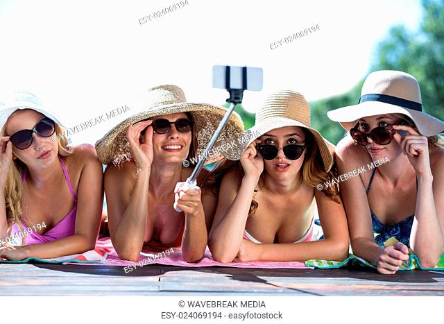 Group of friends taking selfie with selfie stick