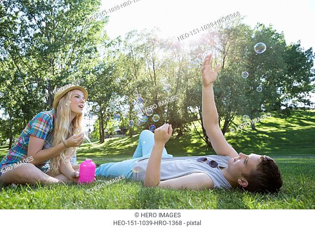 Teens playing with soap-bubbles outdoors