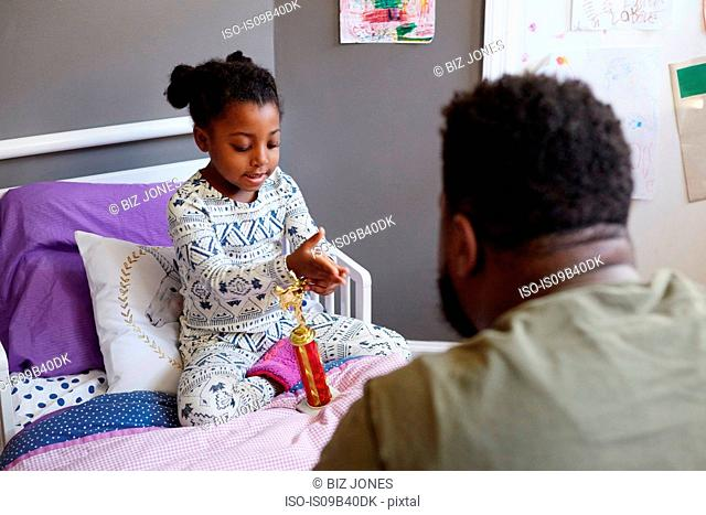 Father talking to young girl on bed with trophy