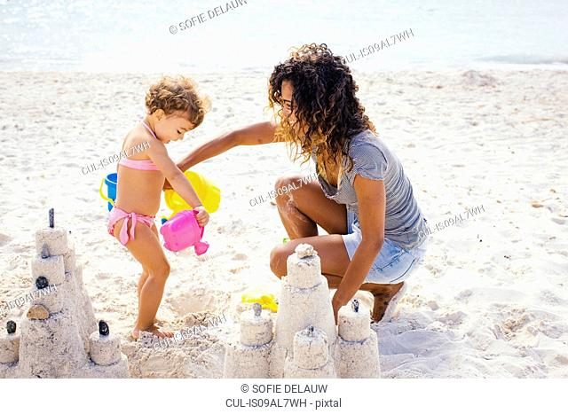 Mother and toddler daughter building sandcastle on beach, Tuscany, Italy