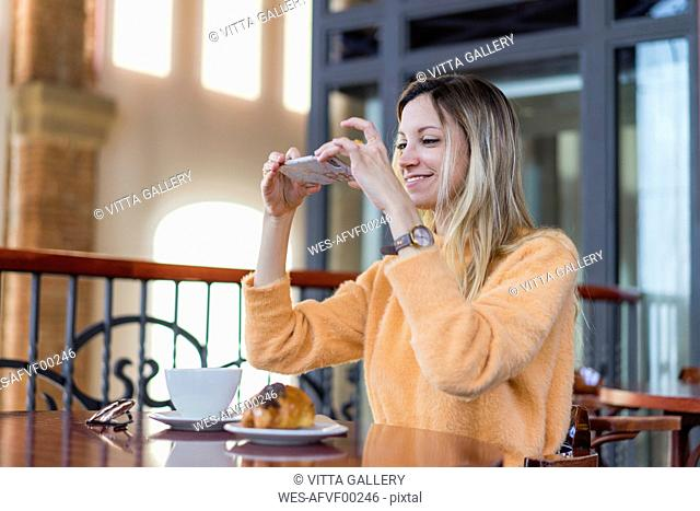 Smiling young woman in a cafe taking cell phone picture