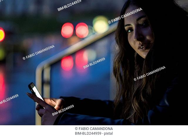 Portrait of Caucasian woman texting on cell phone outdoors