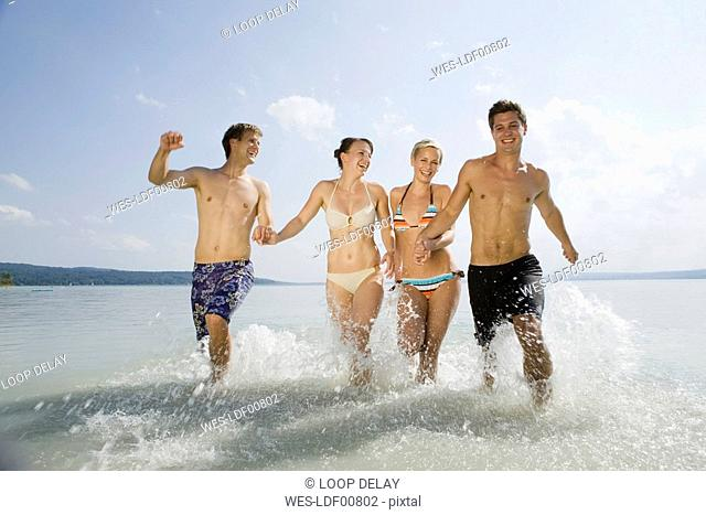 Germany, Bavaria, Ammersee, Young people running into lake