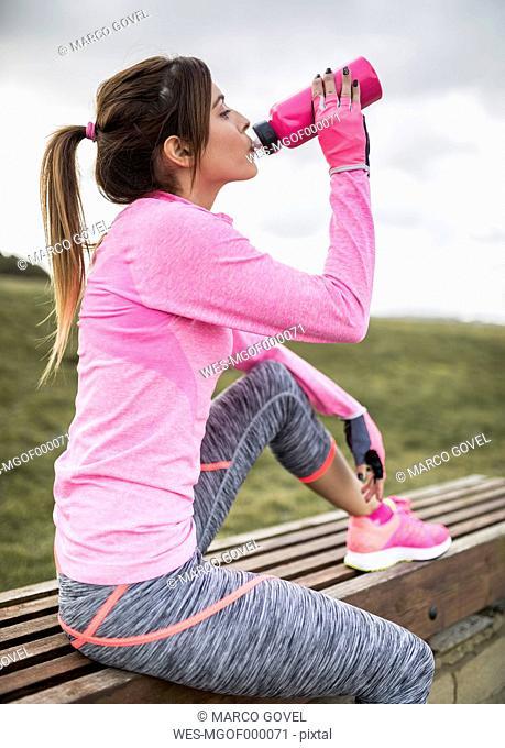 Spain, Gijon, sportive young woman drinking from water bottle