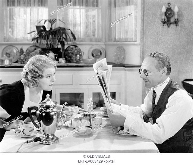 Couple reading newspaper at breakfast table All persons depicted are not longer living and no estate exists Supplier warranties that there will be no model...