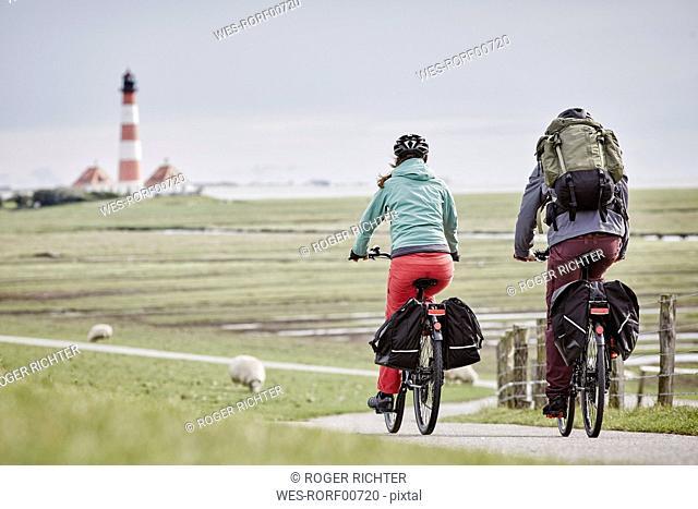 Germany, Schleswig-Holstein, Eiderstedt, couple riding bicycle near Westerheversand Lighthouse