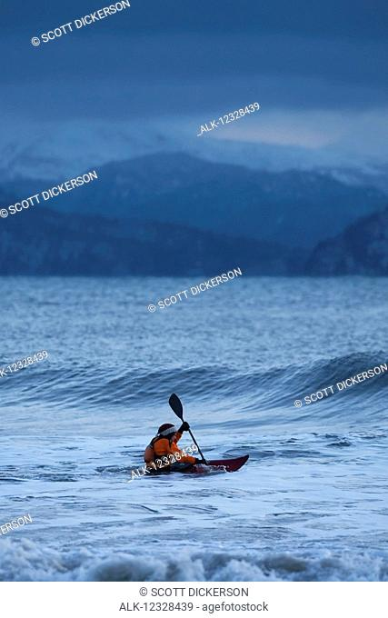Kayak surfer approaching a wave in Kachemak Bay, Southcentral Alaska; Homer, Alaska, United States of America