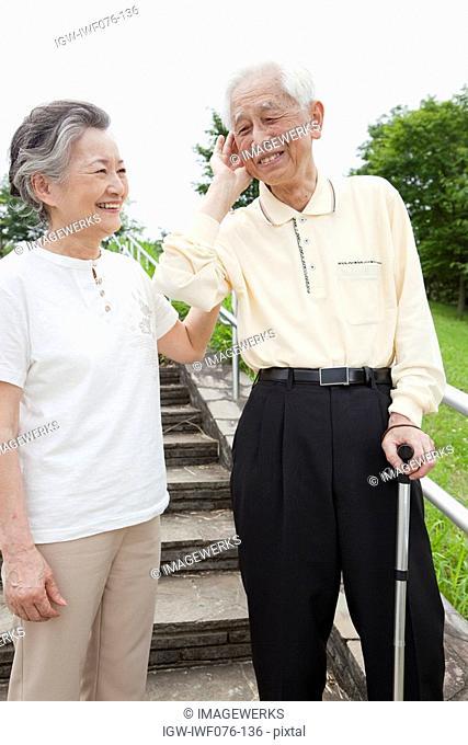 Japan, Tokyo Prefecture, Senior man listening to woman, smiling