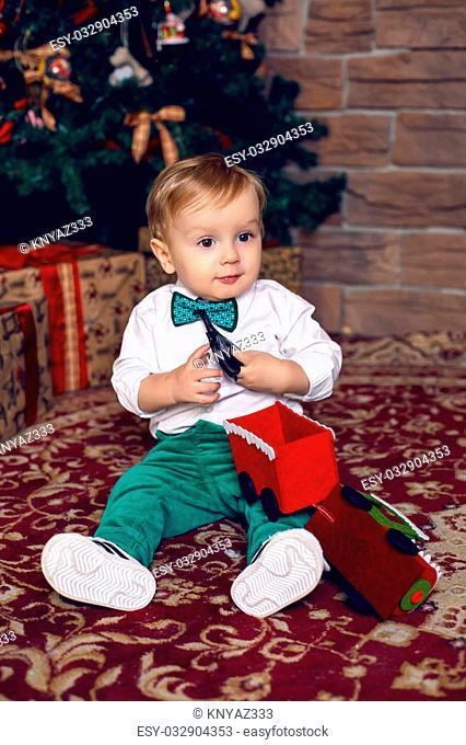 little child sitting on the floor near the Christmas tree in the white shirt and green pants and tie with gifts
