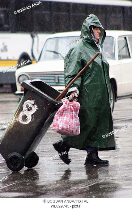 Bucharest, Romania - Street sweeper carrying a garbage bin in front of the Bucharest North Railway Station. Attached to her bin
