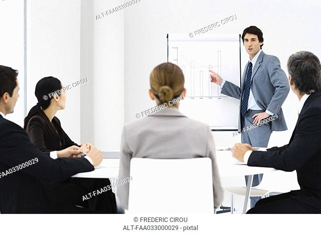 Businessman making presentation, colleagues watching