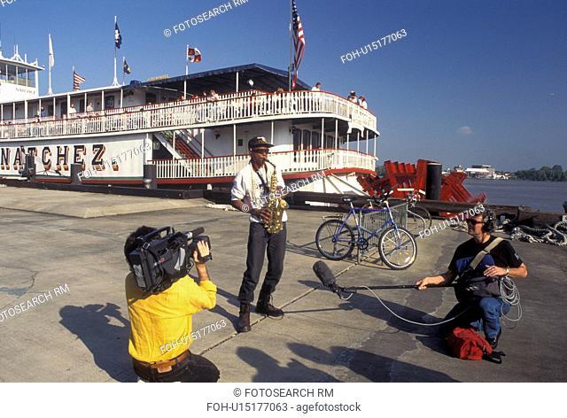 street artist, New Orleans, Mississippi River, Riverfront Park, LA, Louisiana, Men record a street musician playing his instrument on Waldenberg Riverfront Park...