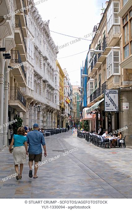 Tourist Couple walk down a Narrow Street in Cartagena, Region of Murcia, Spain