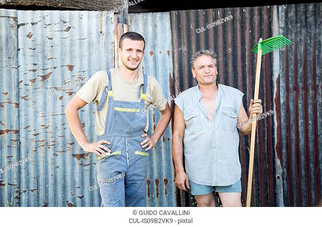 Portrait of two male farmworkers in farmyard
