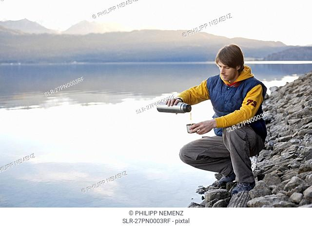Man on lake in mountains with beverage