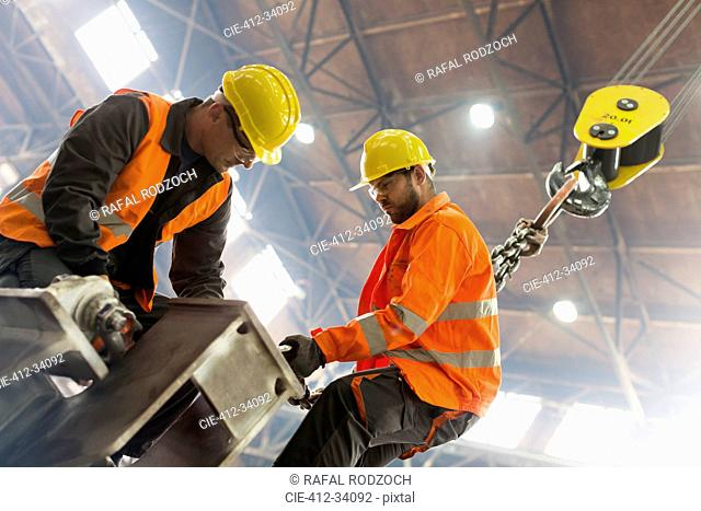Steel workers fastening crane hook to steel in factory