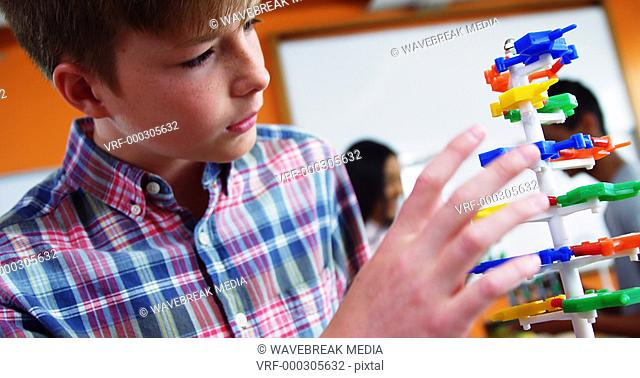 Schoolboy experimenting molecule model in laboratory at school