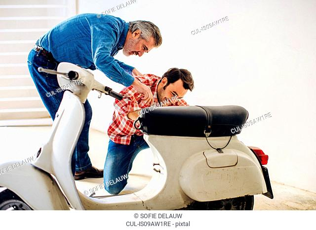 Mature man helping adult son to repair moped in garage