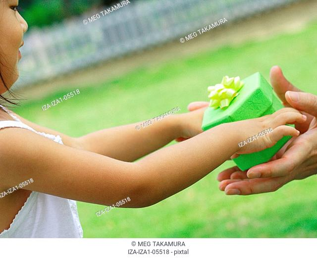 Close-up of a person's hands taking a gift from a girl