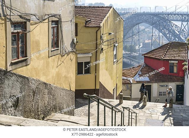 Steps leading down to the River Douro waterfront in the Ribeira district of Porto, Portugal. with the Dom Luis I Bridge in background