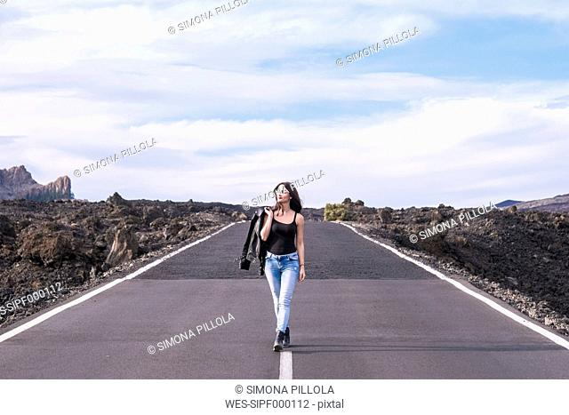 Spain, Tenerife, woman walking on an empty road