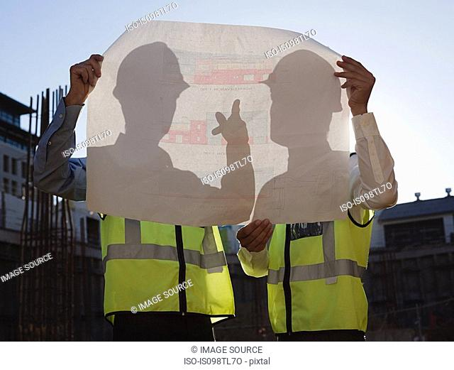Mature men with blueprint on construction site